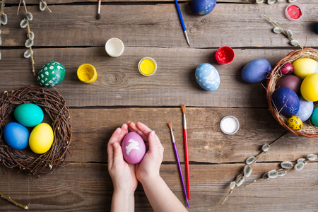 Easter background. colorful eggs in a nest of straw and willow branches and basket on wooden table. the process of painting eggs . childrens hands holding an egg. Top view