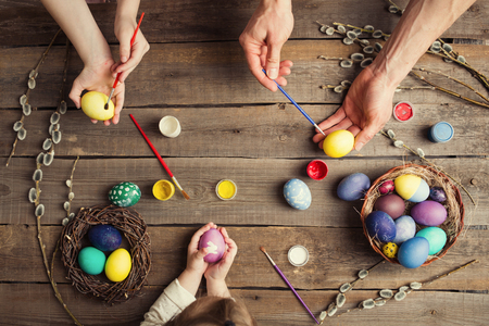 Easter background. colorful eggs in a nest of straw and willow branches and basket, paint and brush on a wooden table. the process of painting eggs . hands of children and parents, brushes and paints.