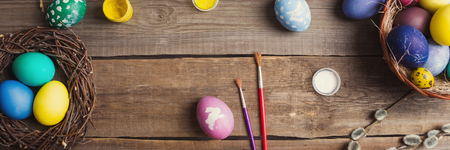 Easter background. colorful eggs in a nest of straw and willow branches and basket, paint and brush on a wooden table. drawing on a stencil in the form of an Easter bunny. 스톡 콘텐츠