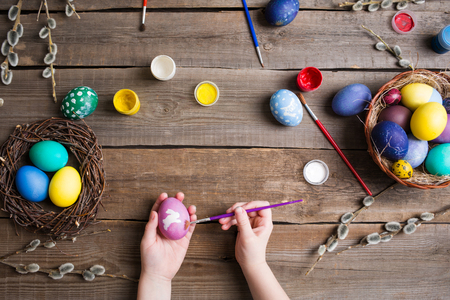 Easter background. colorful eggs in a nest of straw and willow branches and basket on wooden table. the process of painting eggs . childrens hands holding an egg and brush. Top view 스톡 콘텐츠