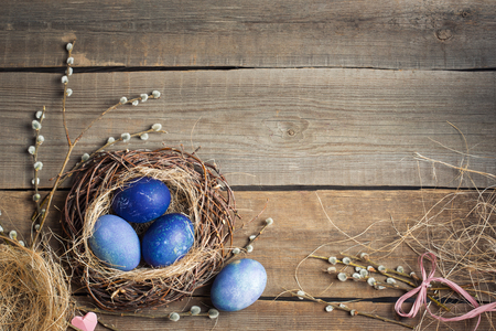 Easter background. blue eggs in a nest of straw and willow branches on a wooden table, copy space 스톡 콘텐츠