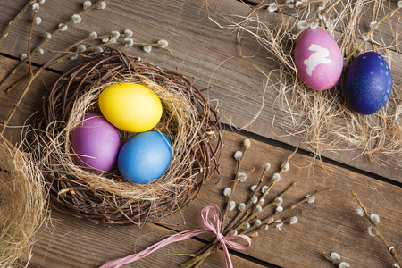 Easter background. colorful eggs in a nest of straw and willow branches on a wooden table. drawing on a stencil in the form of an Easter bunny.
