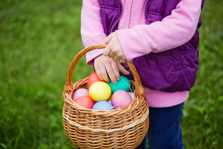Little girl hunts Easter egg. Kids searching eggs in the garden. Child putting colorful eggs in a basket