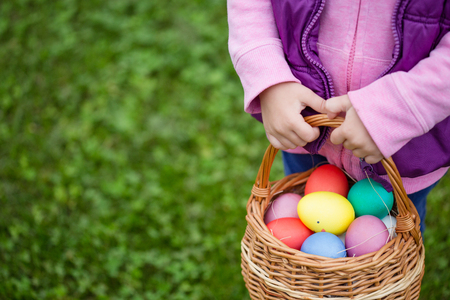 Little girl hunts Easter egg. Kids searching eggs in the garden. Child holds a basket with colored eggs