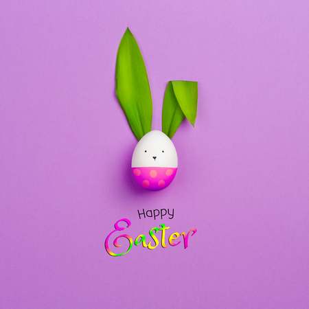 Easter Bunny made of colored egg and green leaves of spring flower on purple background. happy Easter text. minimalism, copy space.
