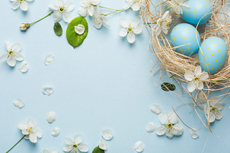 painted blue Easter eggs in the nest on the background of cherry blossoms. Banco de Imagens