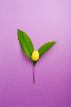 yellow Easter egg as Lily of the valley flower on purple background. minimalism, copy space.