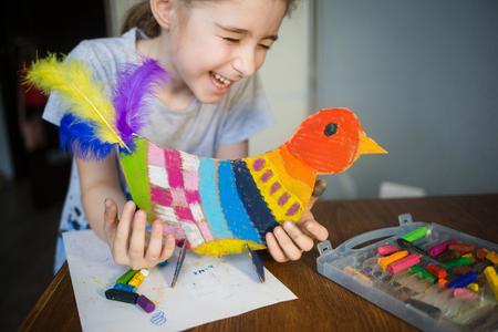 manualidades con niños. pájaro brillante, cortado de cartón y pintado con crayones de cera, en manos de un niño. proceso de creación.