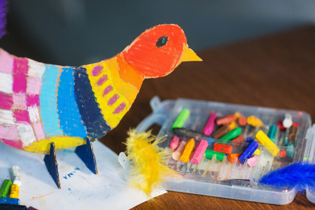 craft with kids. bright bird, cut from cardboard and painted with wax crayons. process of creating.
