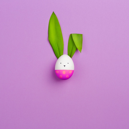 Easter Bunny made of colored egg and green leaves of spring flower on purple background. minimalism, copy space.