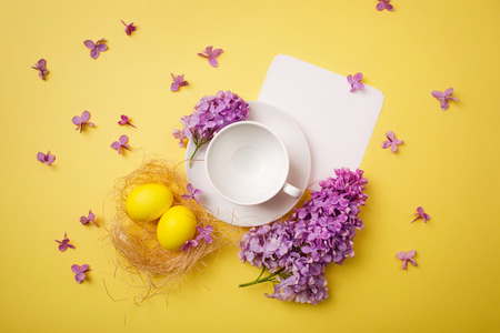 Easter egg, white empty coffee Cup on bright yellow background with branches and purple lilac flowers. copy spase, flat lay.