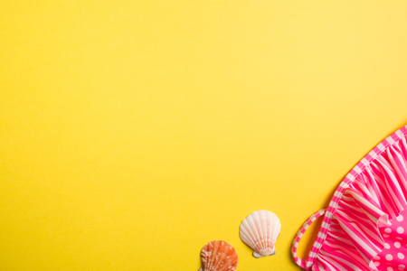 swimsuit and seashells on yellow background. copy space, top view.