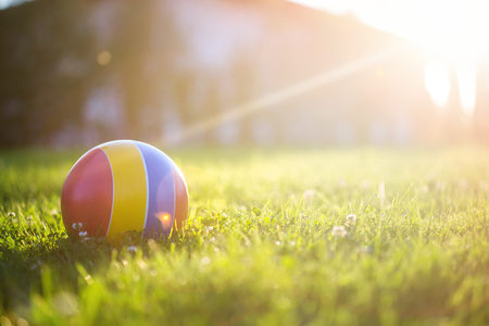 childrens rubber ball on the grass. On a Sunny summer day Banco de Imagens