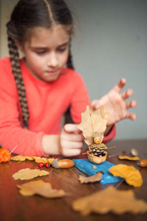 autumn craft with kids. children's cute boat with man made of natural materials. process of creating. Imagens