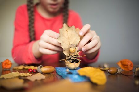 autumn craft with kids. childrens cute boat with man made of natural materials. process of creating.