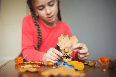 autumn craft with kids. children's cute boat with man made of natural materials. process of creating.