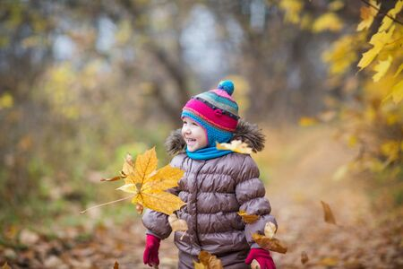 happy little child, baby girl laughing and playing leaves in the autumn on the nature walk outdoors