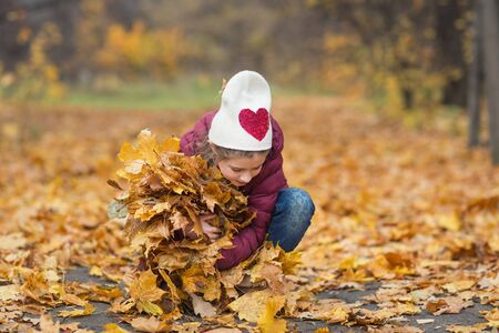 happy child, girl holding an armful of autumn yellow leaves on the nature walk outdoors Banco de Imagens