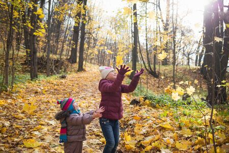 happy little children laughing and playing leaves in the autumn on the nature walk outdoors. life style