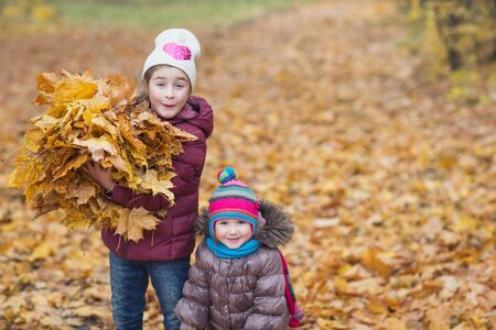happy children. girl holding an armful of autumn yellow leaves on the nature walk outdoors