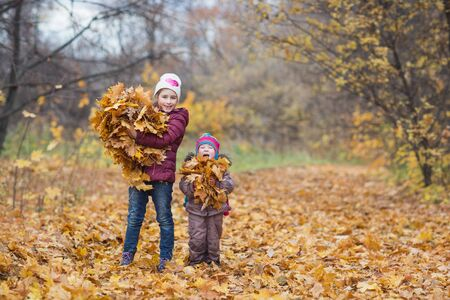 happy children. girl holding bunch of autumn yellow leaves on the nature walk outdoors