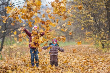happy children. girls throw up autumn yellow leaves on the nature walk outdoors. maple leaf fall in the Park Banco de Imagens