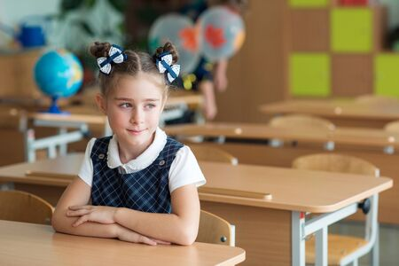 First-grader girl with bows on the first day of school at the Desk