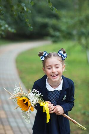 First grader girl with bows and bouquet in the first day of school. the student laughs.