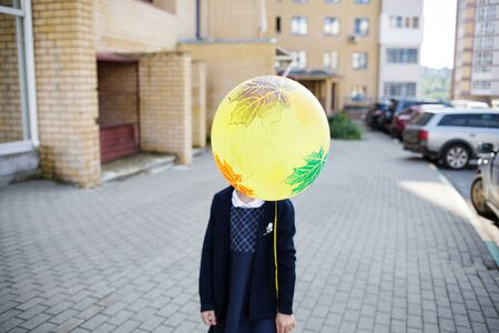 First-grader girl on the first day of school. girl with a ball in her hand. ball as head.
