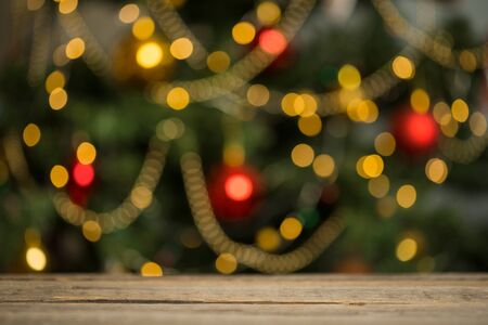 rustic wood table in front of christmas light night, abstract circular bokeh background.