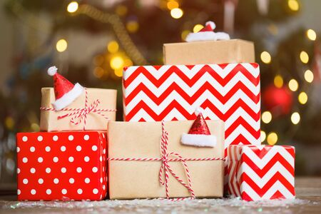 gifts in red wrapping paper on Christmas tree background. stack of boxes under the tree.