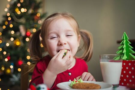 the child eats candy on the background of a Christmas tree with lights. childrens xmas dinner.