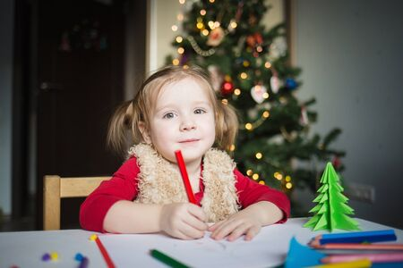 the child writes a letter to Santa Claus. a little girl draws with crayons on the background of the Christmas tree. the concept of new year kids creativity.