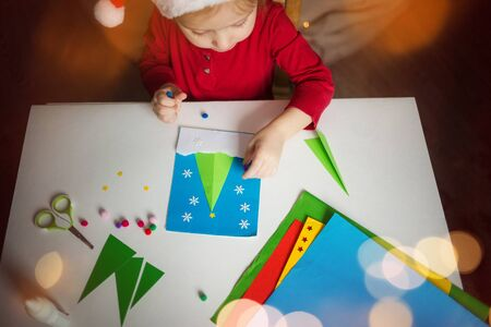 a little girl makes a card application of colored paper with the Christmas tree. the concept of winter kids creativity. Stock Photo