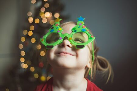 child in funny glasses in the form of Christmas trees on the background of lights. girl looks up.