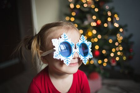 child in funny glasses in the form of snowflakes on the background of lights. Banco de Imagens