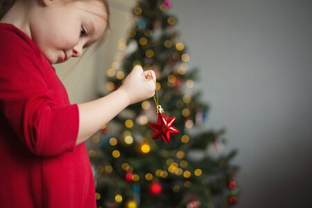 a small child decorates the Christmas tree. girl holding a Christmas toy in her hands.