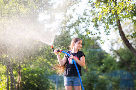 child uses hose to water plants in garden in Sunny hot summer day. kids fun. girl waters herself from shower. tool for pour.