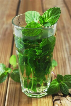 A Glass Of Peppermint Tea On A Wooden Background