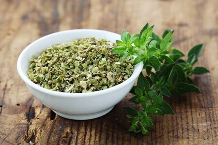 Dried Oregano In A White Bowl On A Wooden Background