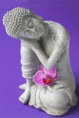Buddha Figure With An Orchid On A Purple Background Reklamní fotografie