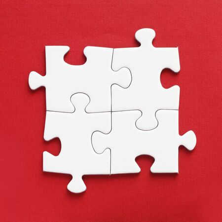 White Jigsaw Puzzle Pieces On A Red Background 写真素材