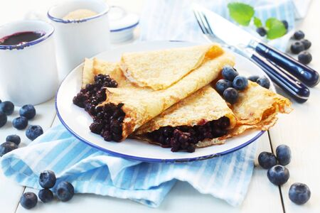 Crepes With Blueberries On A Blue And White Background