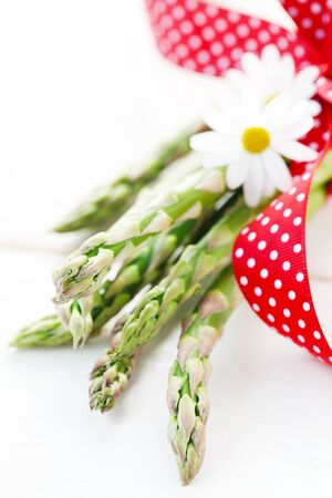 Green Asparagus With A Red Ribbon On A White Background