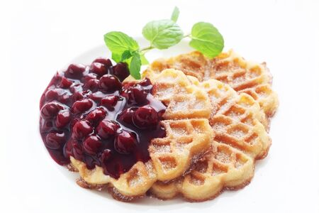 Waffles With Cherry Sauce On A White Plate