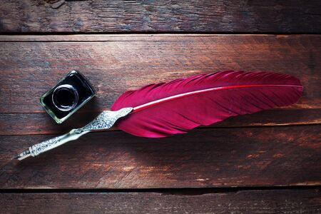 A Red Quill And An Inkwell On A Wooden Background 版權商用圖片