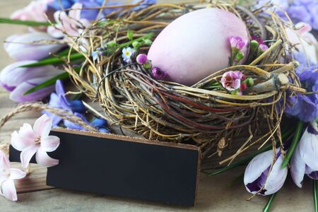 Easter Nest WIth A Purple Egg And A Blank Slate On A Wooden Background 版權商用圖片