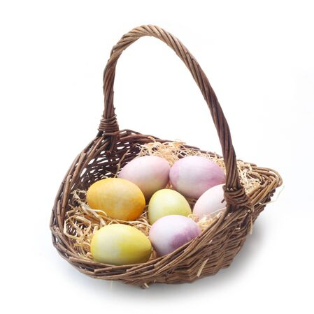 Easter Eggs In A Wicker Basket Isolated On White