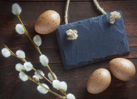 Easter Eggs, Catkins And A Blank Slate On A Wooden Background