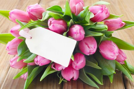 A Bunch Of Tulips With A Blank Paper Label On A Wooden Background